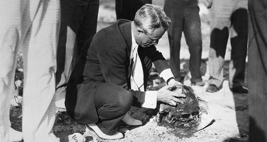 A crime scene investigator observing the decapitated head of a victim of the Cleveland Torso Murderer.