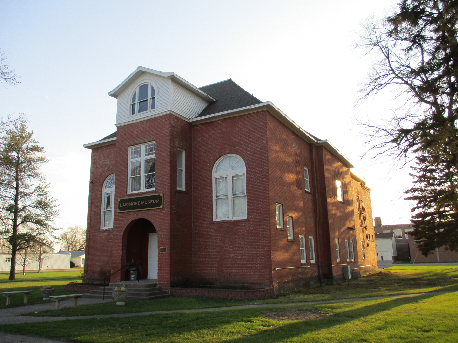 Old Larimore City Hall in the evening. This image shows the east (front) and north sides of the building. Evidence of the removed large Colonial Style fanlight window can be seen on the second floor of the north side.