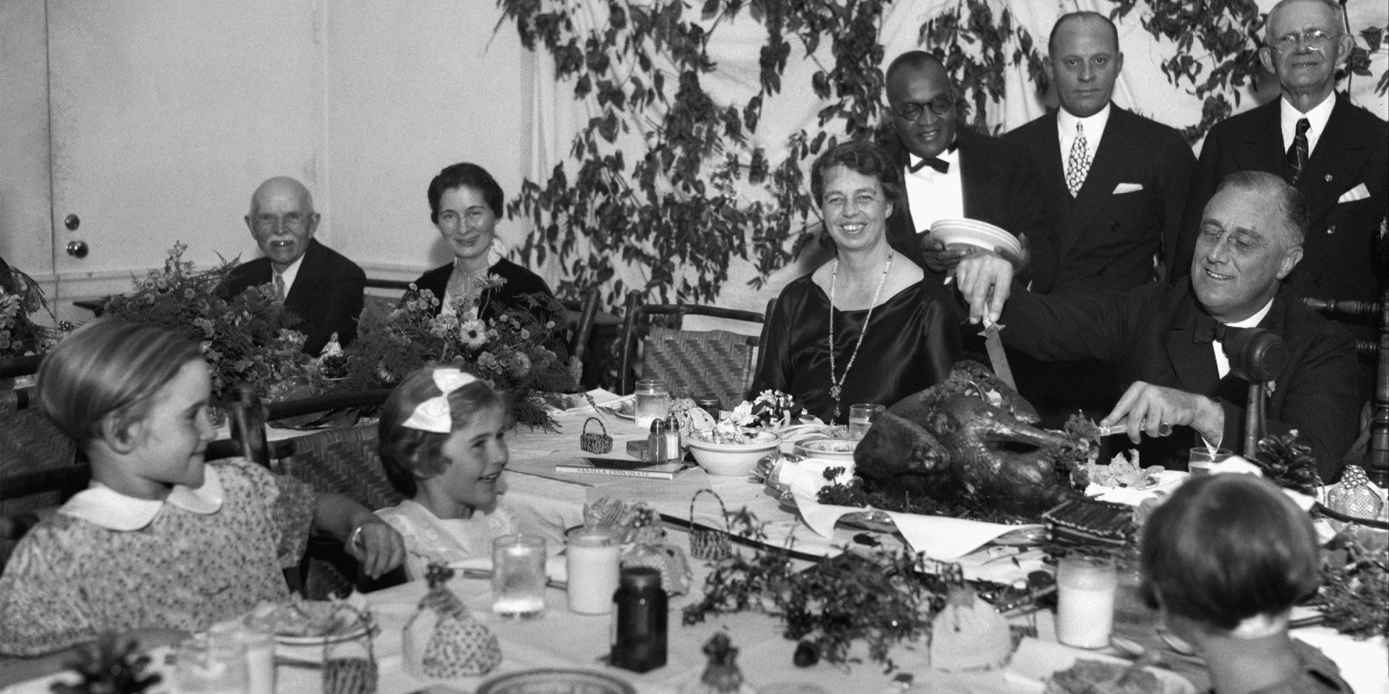 President Franklin D. Roosevelt, accompanied by Eleanor Roosevelt, carves the 1933 Thanksgiving Day turkey with fellow polio patients in the Georgia Hall Dining Room.