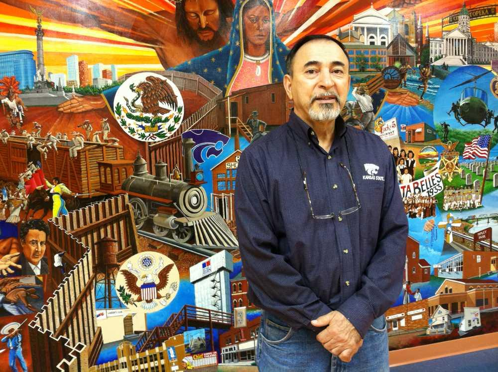 "Topeka Native Andy Valdivia stands in front of the large, colorful mural he painted in the basement of the Marlo Cuevas-Balandran Activity Center, 216 N.E Banner. The mural, titled ""Our History"", depicts the Mexican-Hispanic heritage of Our Lady of G"