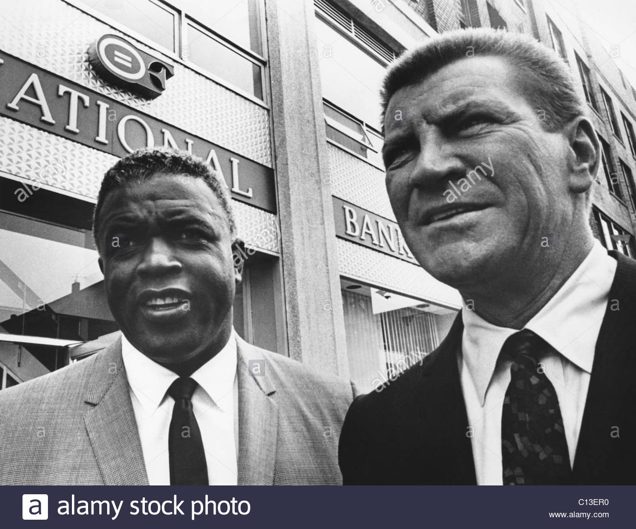 Jackie Robinson, with Robert Preston in front of the Freedom National Bank in Harlem, 1965 -