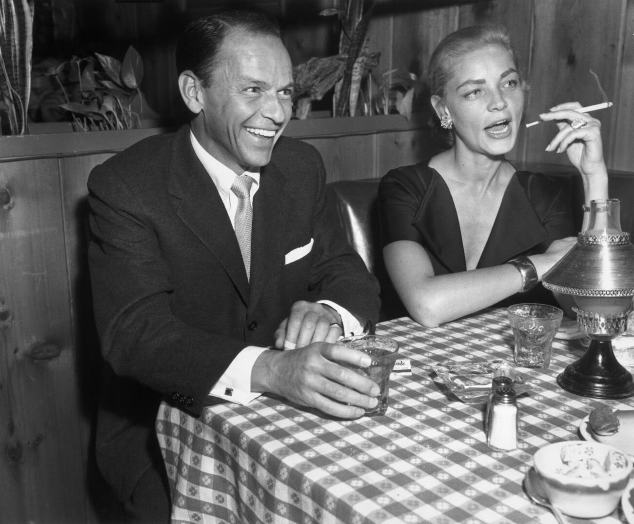 Singer and actor Frank Sinatra with actress Lauren Bacall at Musso and Frank, 1957