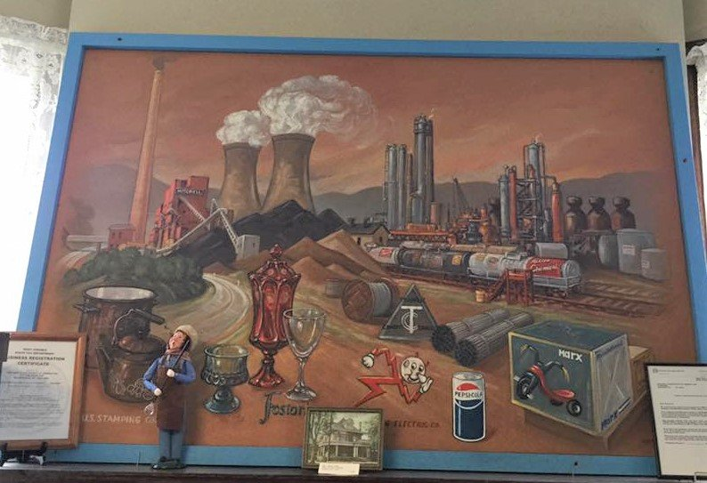 Local residents might recognize this picture that once hung in a local bank. It represents the many industries once present in Marshall County. Now the painting hangs in the main entrance to the Fostoria Glass Museum.