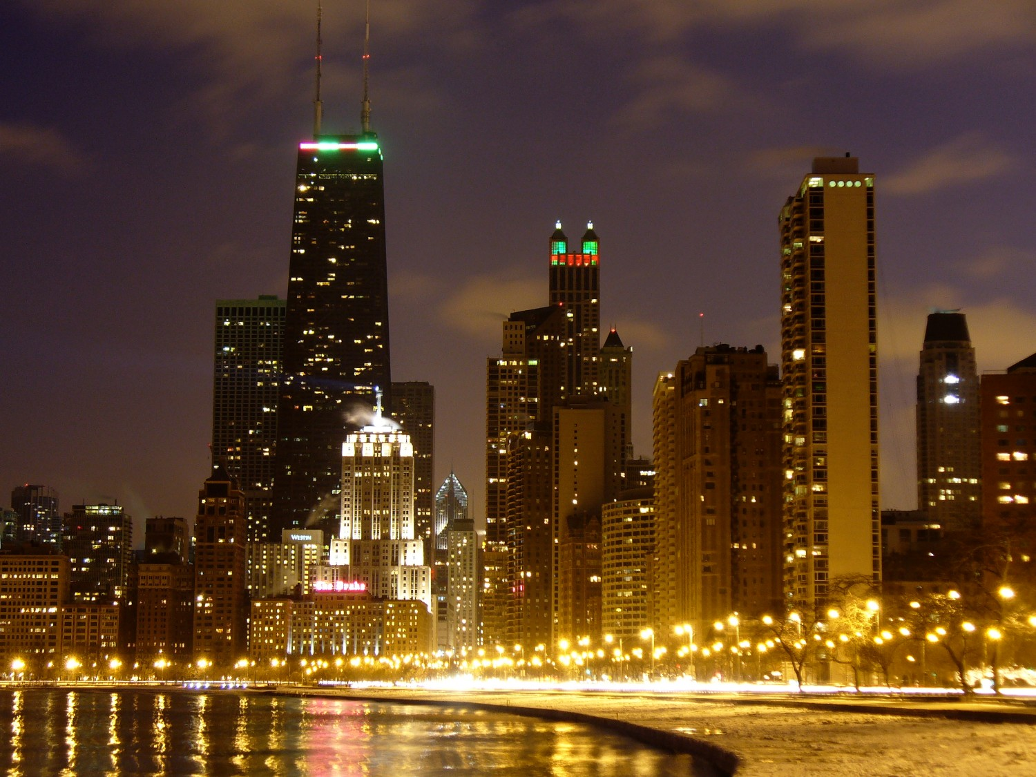 Oak Street Beach View: This is a photograph of Oak Street Beach in Chicago, IL on a cold night in January. The road in this picture is Lake Shore Drive. The bright, art deco building with the lit beacon is the Palmolive Building.