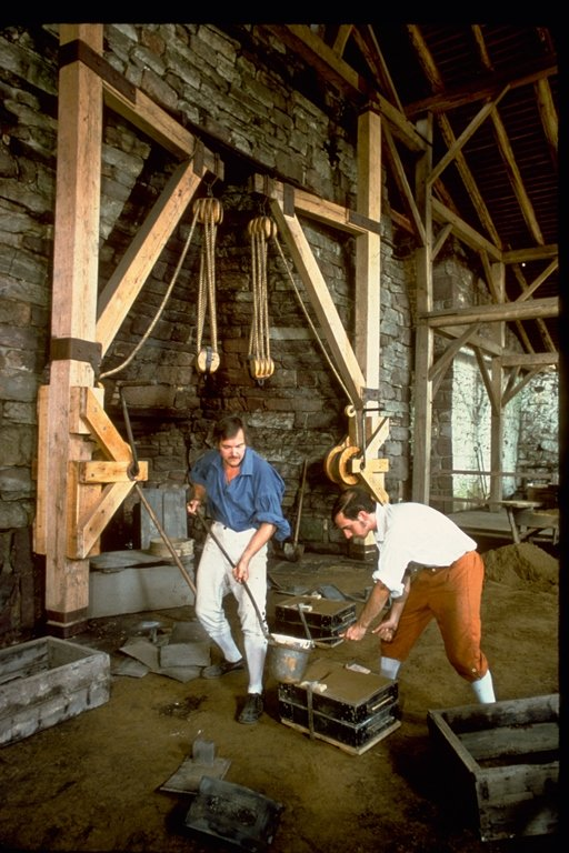 Two period actors fill a sand mold with molten iron.