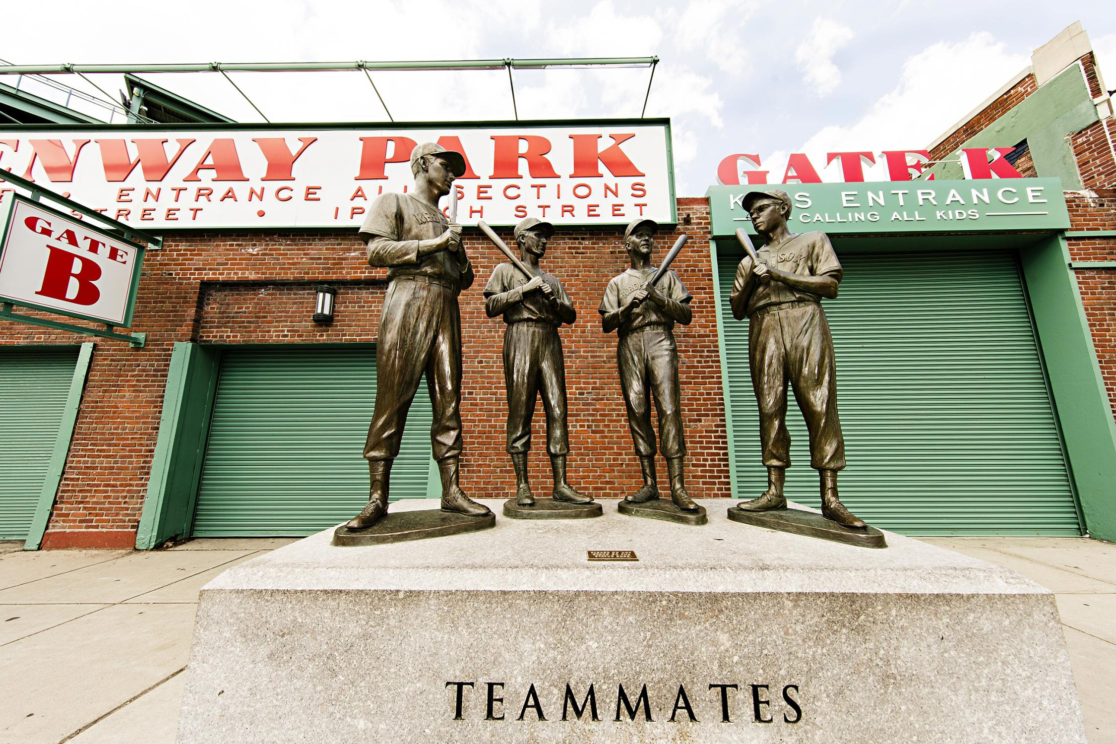 """The statue as seen with Fenway Park's Gate B in the background, the pedestal inscribed with the word """"Teammates"""" can be seen the the foot of the image"""