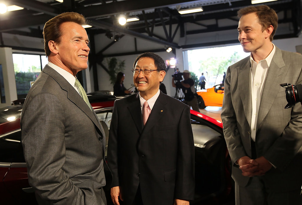 Former California Governor Arnold Schwarzenegger (left) meets with Tesla Motors CEO Elon Musk (far right) and Toyota CEO Akio Toyoda meet to commemorate the sale of the former NUMMI facility to Tesla in 2010. Getty Images.