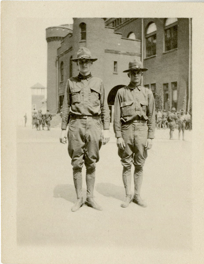 Photograph of two World War I soldiers posed in front of the Red Gym in Madison, Wisconsin.