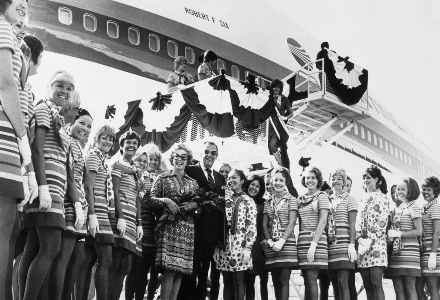 Robert F. Six with his wife, actress Audrey Meadows, and Continental Airlines flight attendants at the dedication of Continental's Boeing 747 named after Six, 1971