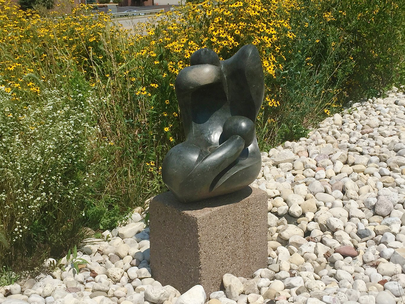 "Laxon Karisi's ""Human Suffering."" The sculpture is made of serpentine, a type of rock with a naturally rough, greenish appearance, similar to a snake."