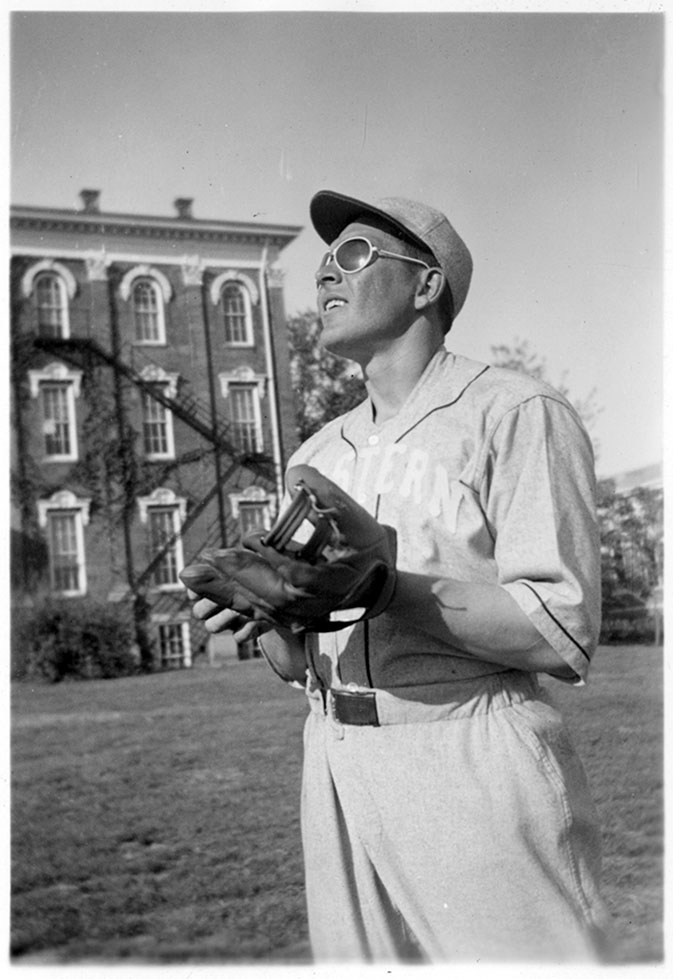 An unidentified baseball player with the University Building in the background.  ca. 1930s.  EKU Photograph Collection.