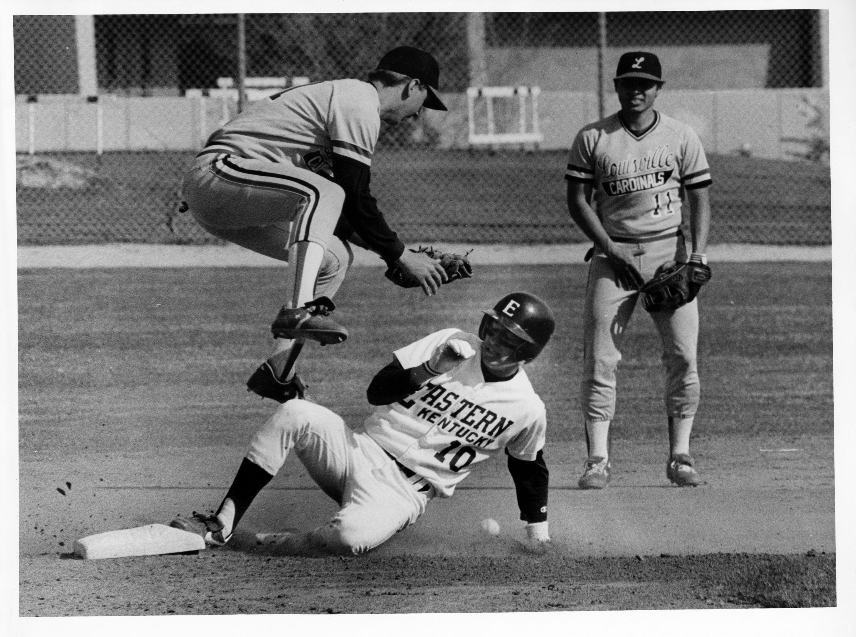 An Eastern baseball player sliding into base in a game against the University of Louisville.  1970s.  EKU Photograph Collection.