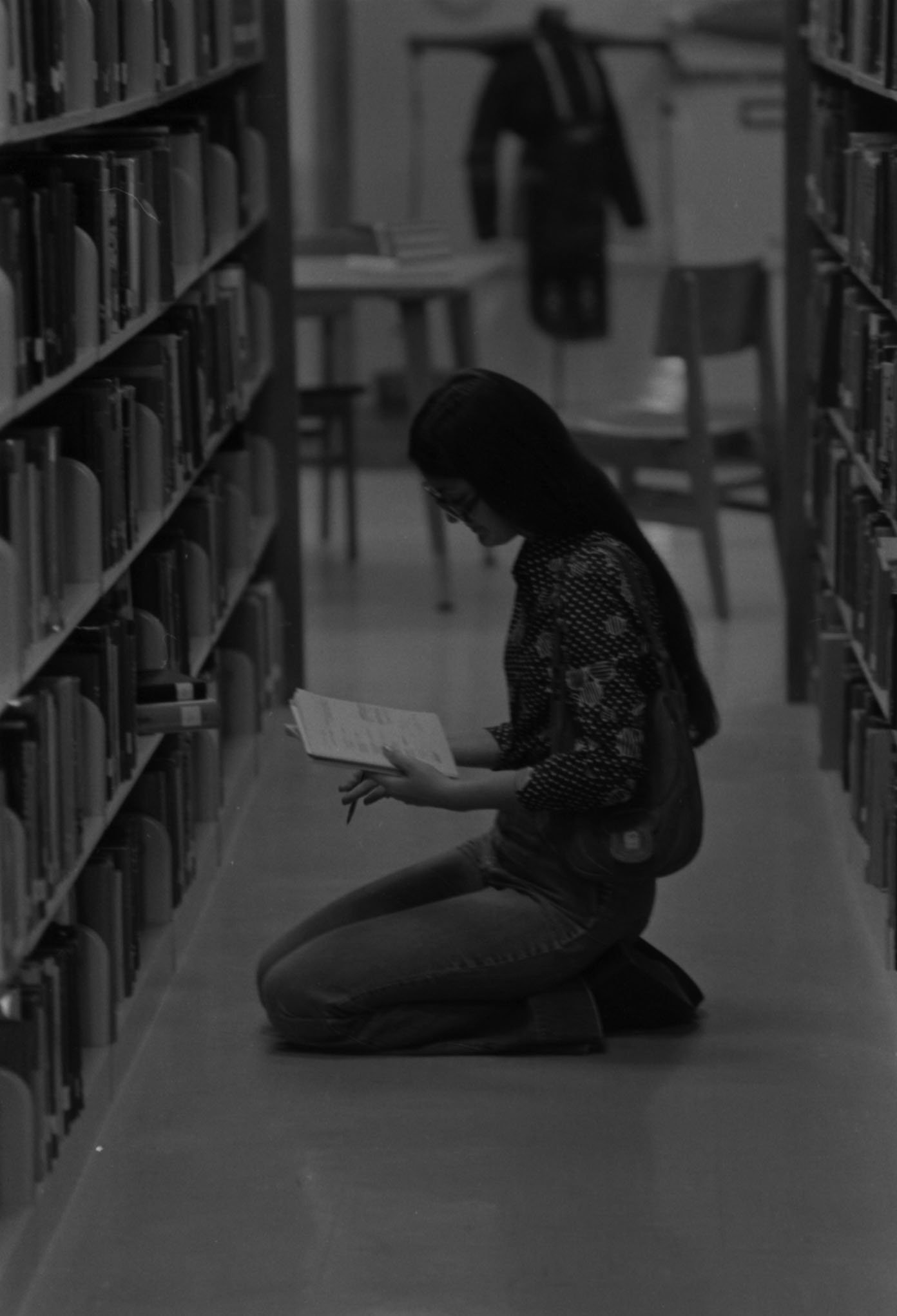 Student looking at a book in a book stack aisle, 1975. EKU Negatives Collection.