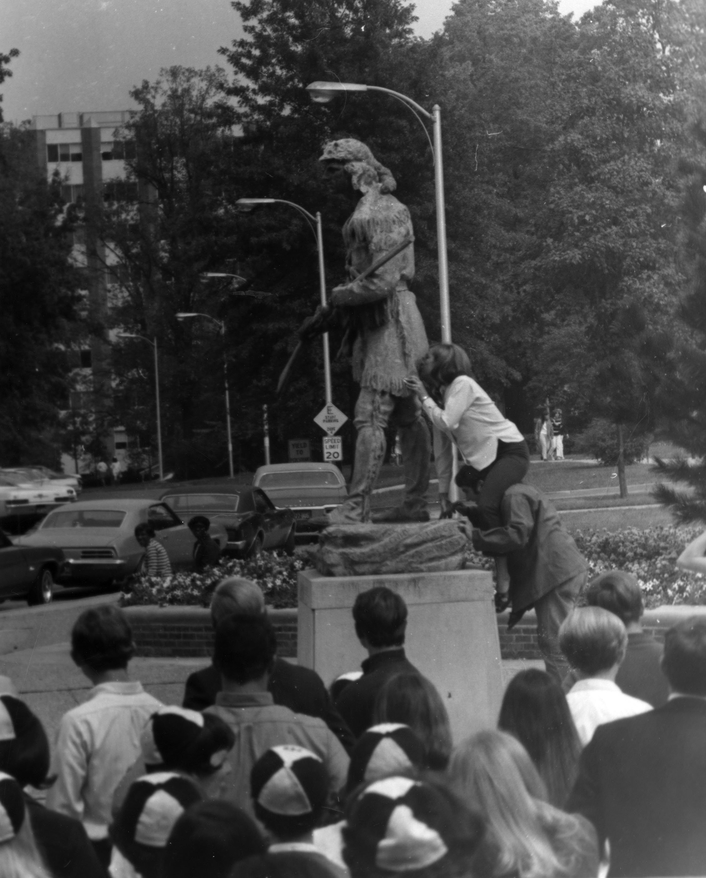 Freshman girl kissing the butt of the Daniel Boone statue during rat court, a hazing of freshman, 1969. EKU Photo Collection.
