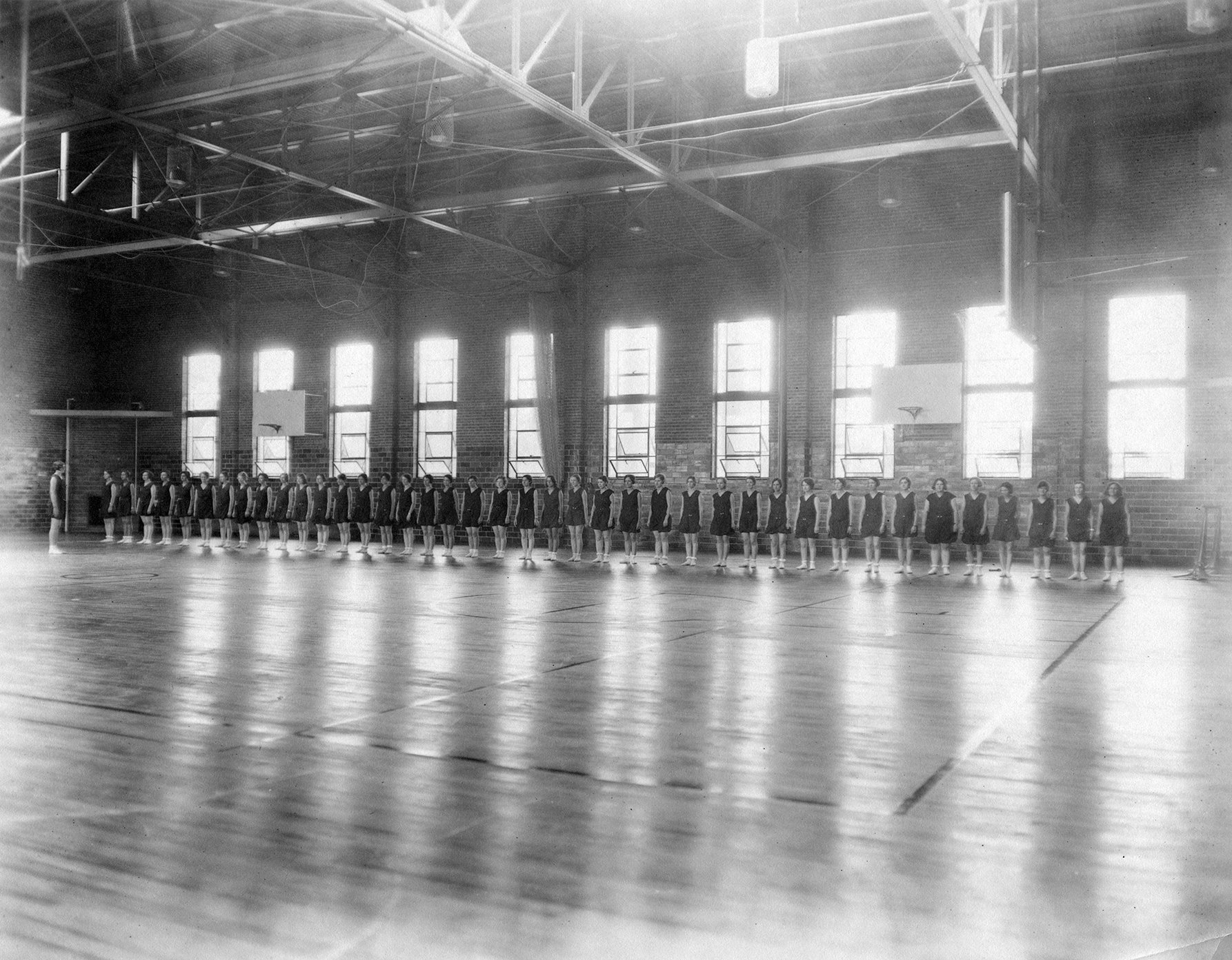Girls lined up along the edge of the basketball court in Weaver Gym, 1935. EKU Photo Collection.