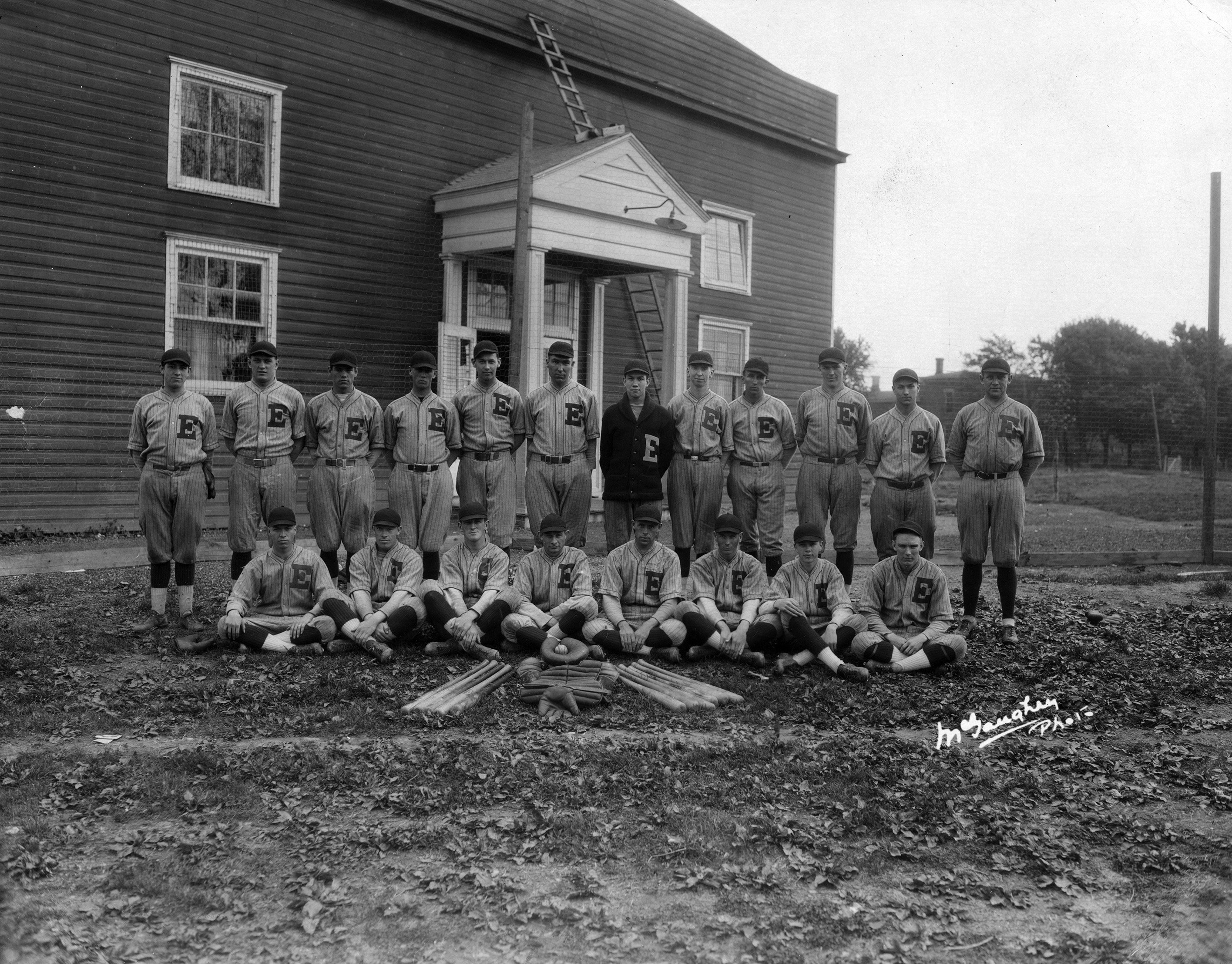 "The 1925 baseball team in front of the Temporary Gymnasium, fondly referred to as the ""Barn."""