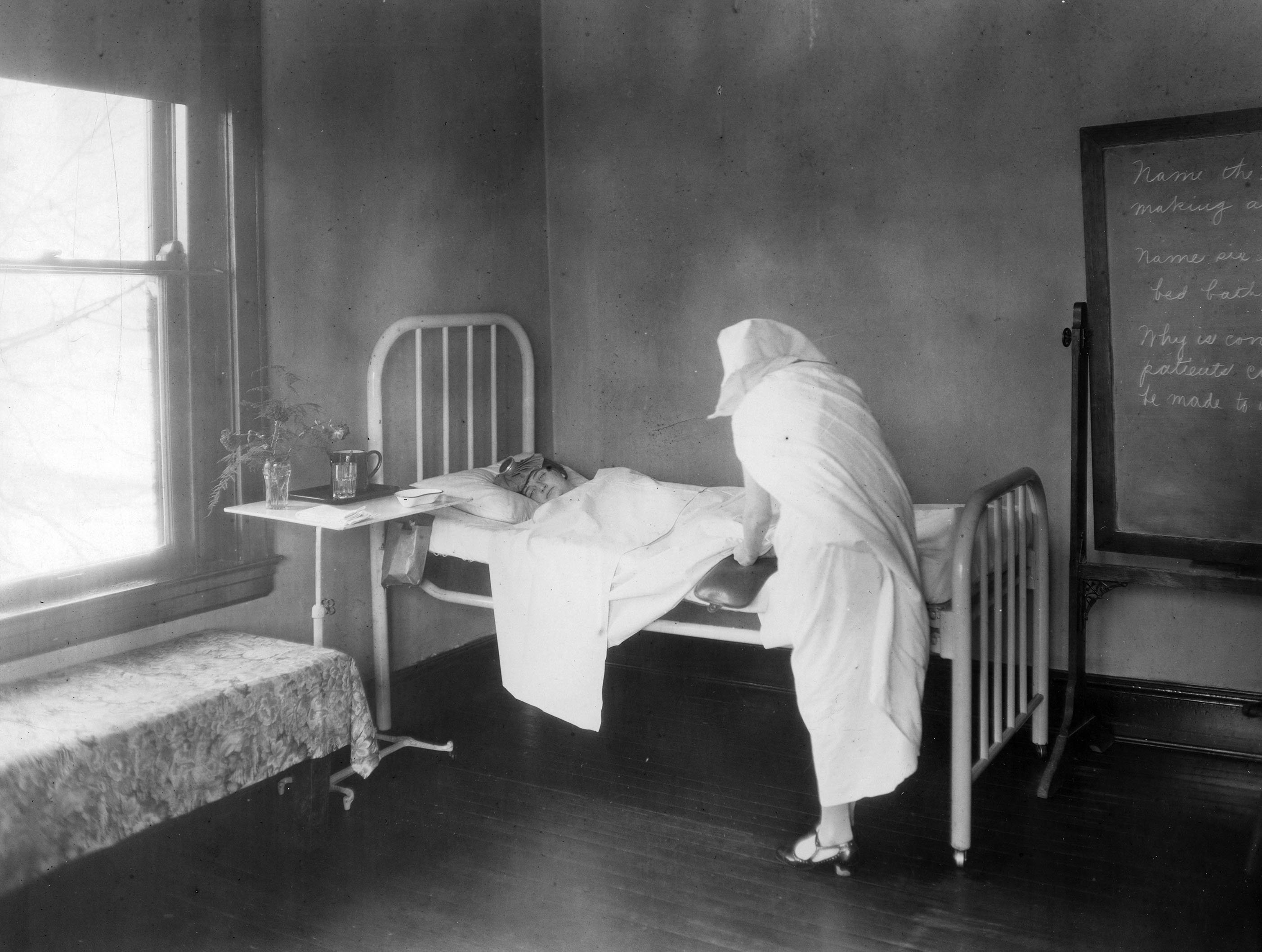 A posed shot with a nurse and patient in the Infirmary when it was located in Cottage 2, 1912.  EKU Photo Collection.