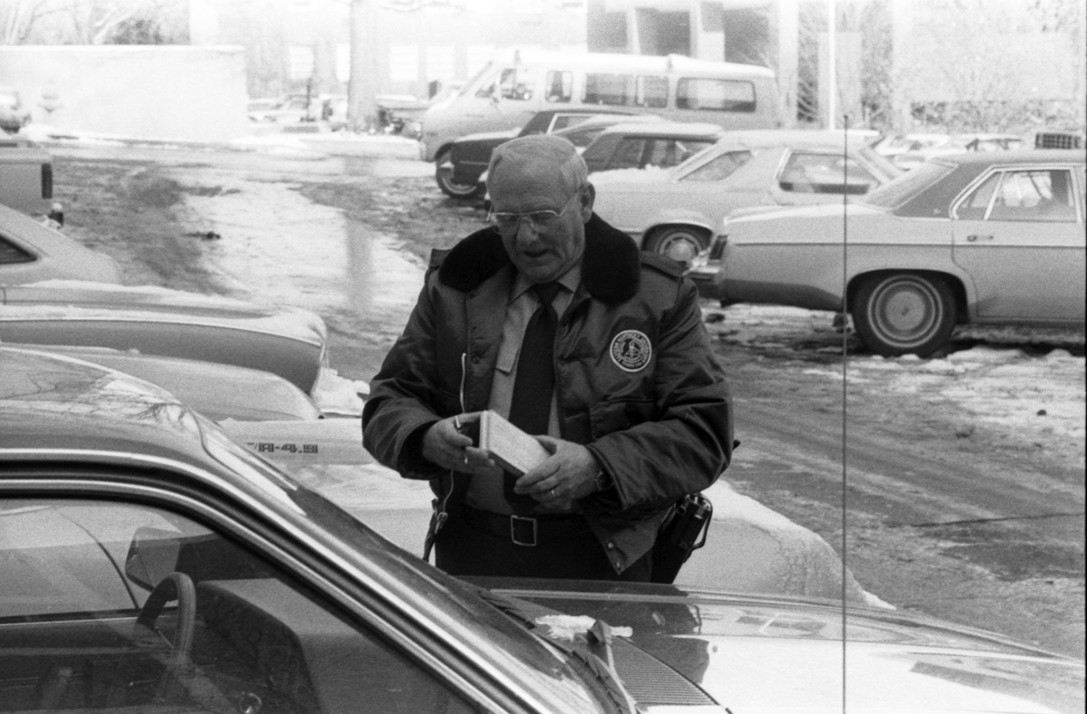 One of EKU's lot guards writing parking tickets, 1984.  EKU Negative Collection.