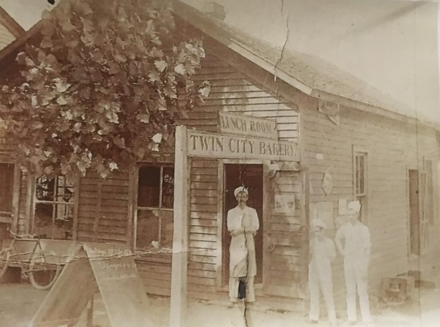 A photo of Charles Thomas in front of his first bakery, the location of which is currently unknown.