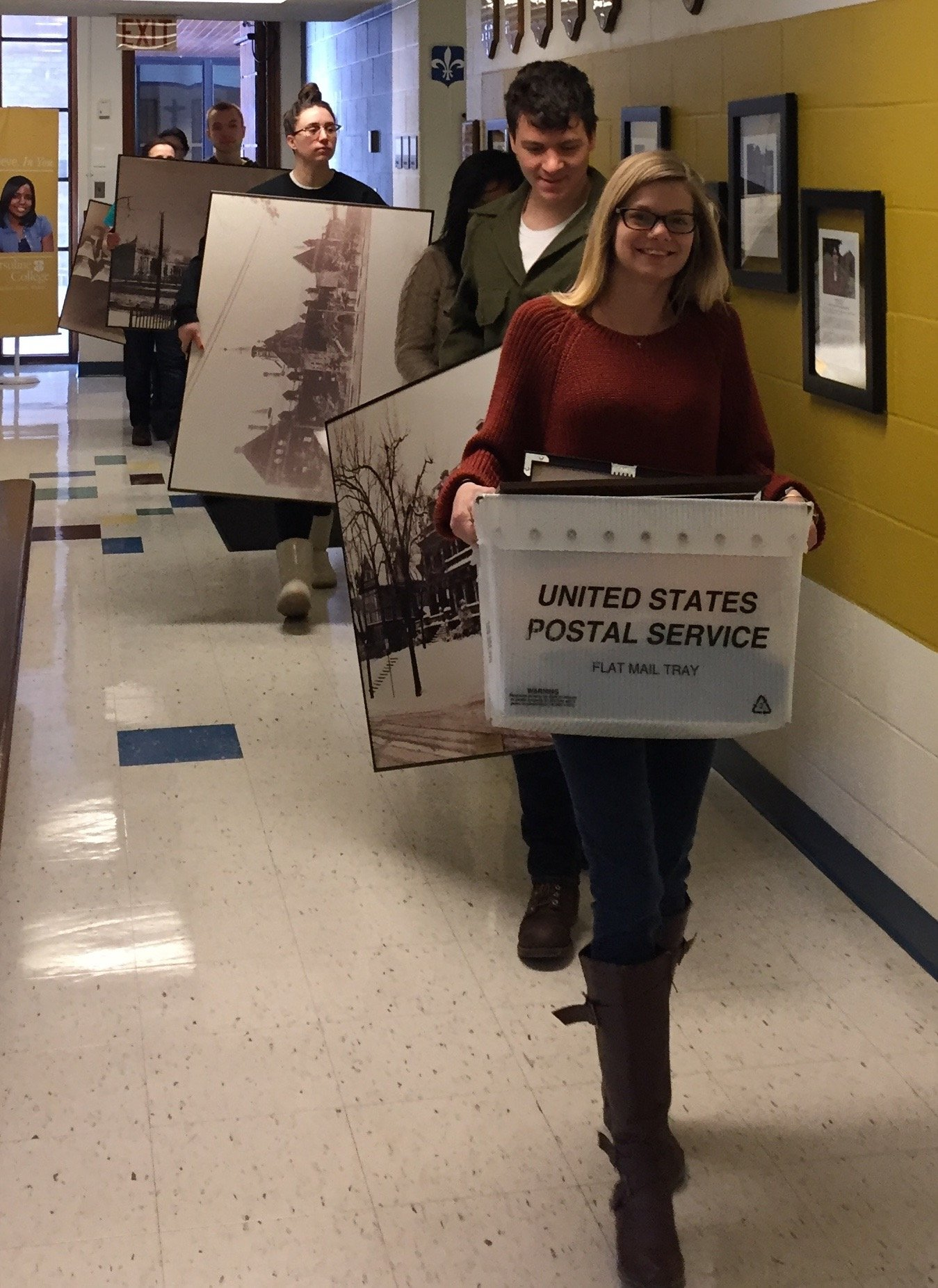 Students from the Designing Ursuline exhibit team gather already framed photographic prints from various departments around Ursuline College for display at the anniversary exhibit in Wasmer Art Gallery, Ursuline College, Spring 2017.