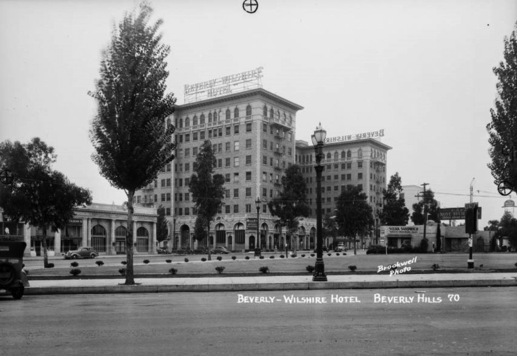 "The Beverly Wilshire Hotel ca. 1930 seen from North Beverly Drive. To the far right the sign for the classic ""Brown Derby"" restaurant can be seen."