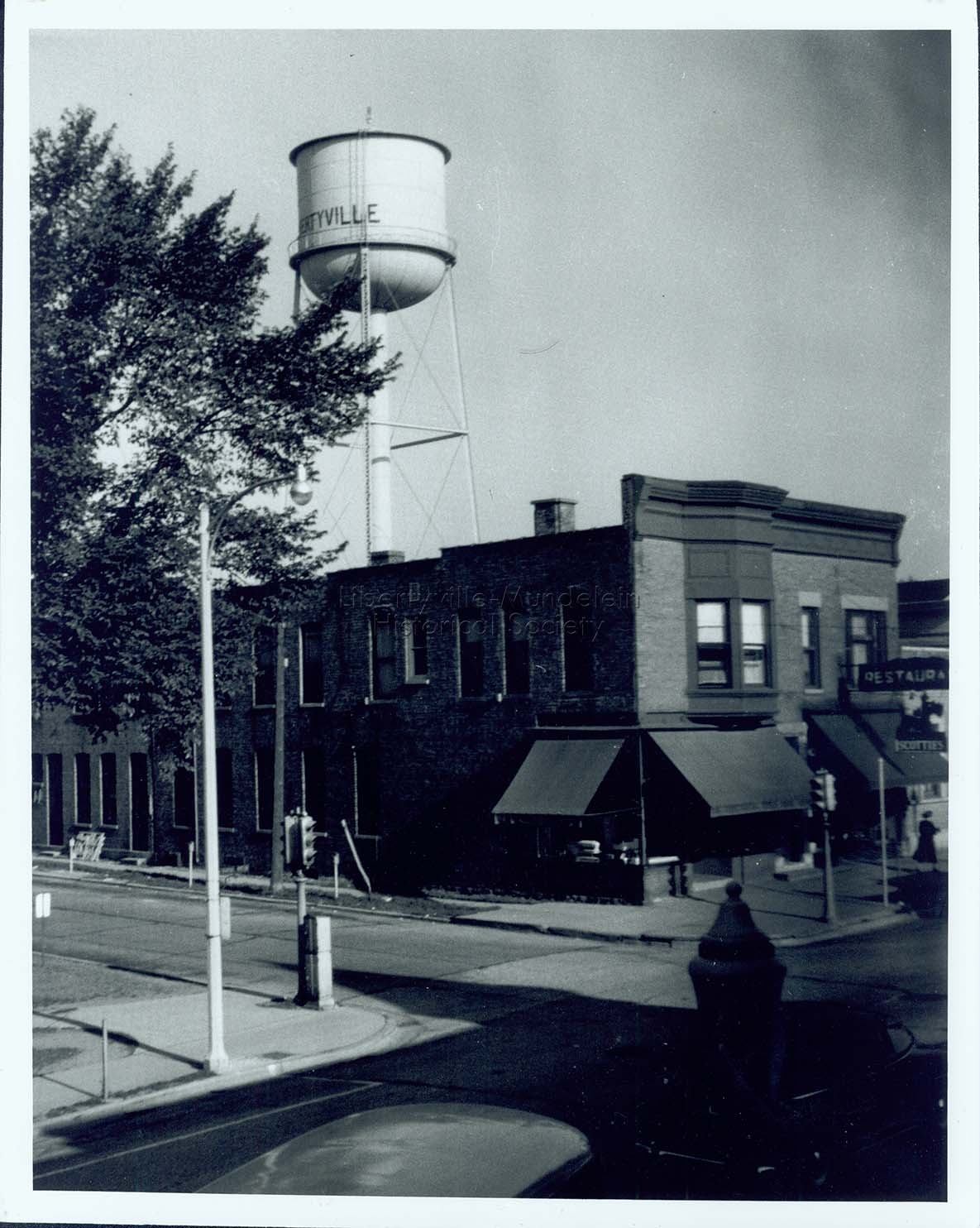 Titus Brothers and Scottie's Restaurant with old village water tower in background, 1948
