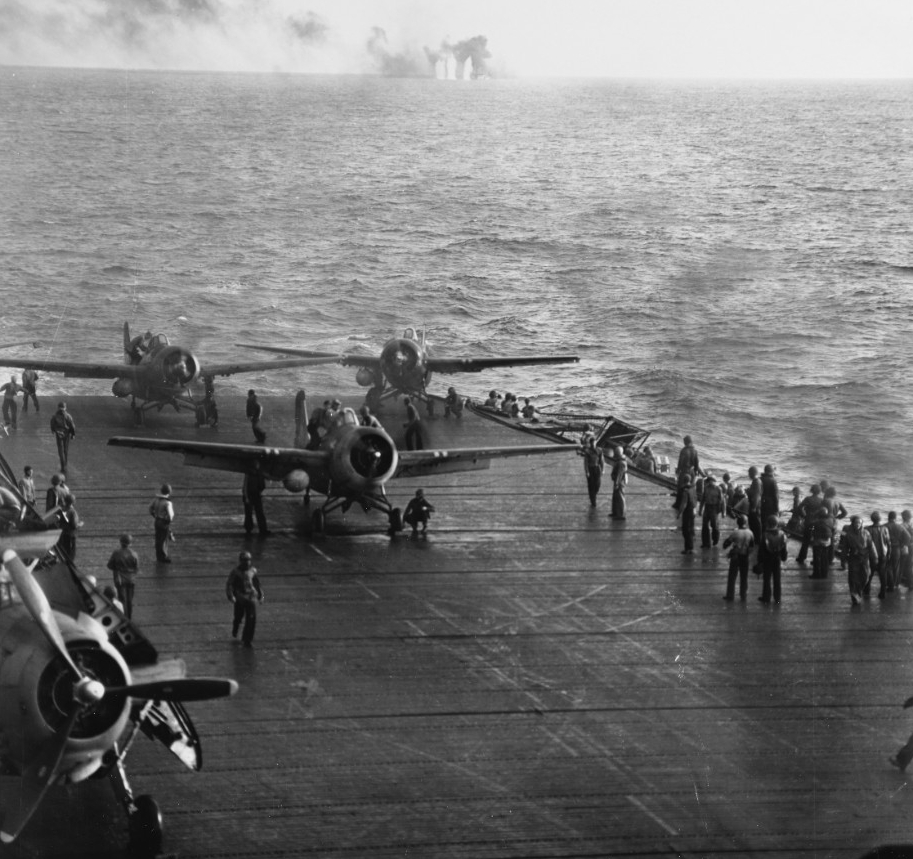 Wildcat fighters launching off USS Kitkun bay as, in the background, shells straddle the White Plains