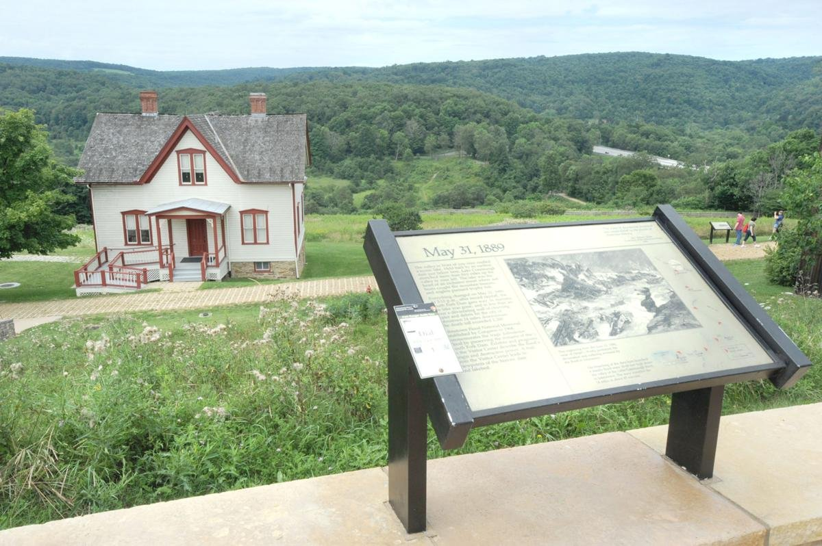 An informational placard with the Unger House in the background.