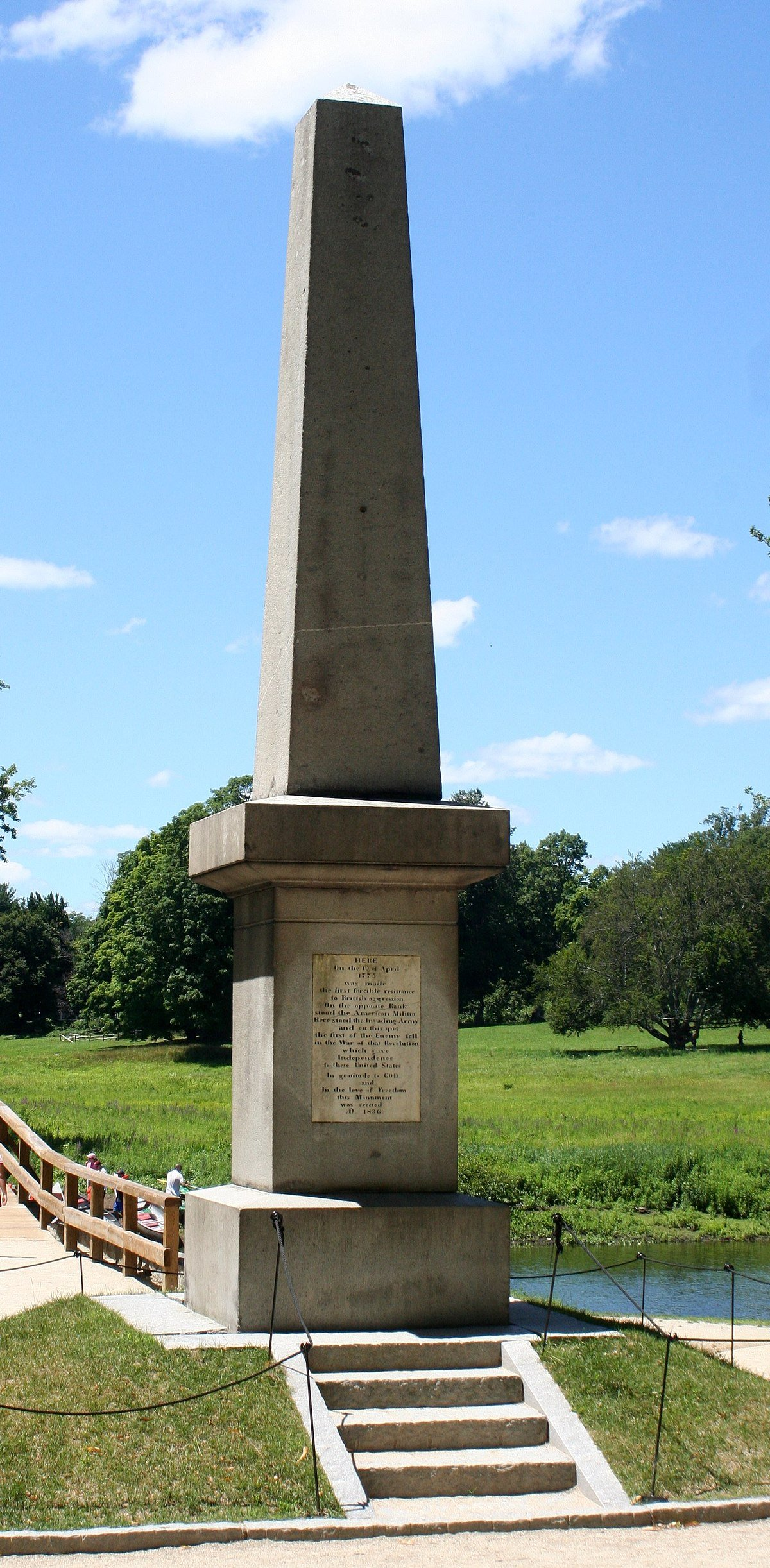The memorial stands on the eastern side of the Old North Bridge. The inscription is visible at the base of the monument.