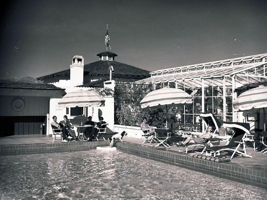 Visitors lounging by the pool at the Palm Springs' Racquet Club, ca. 1948