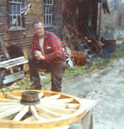 Ben Thresher admiring one of his wagon wheels which was crafted within his mill.