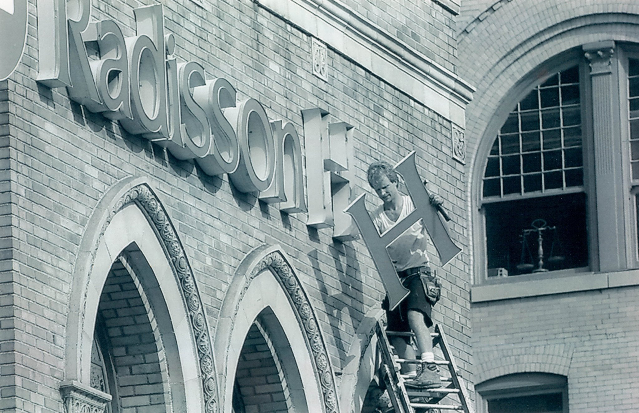 A worker removes the Radisson sign from the Americus in 1994.