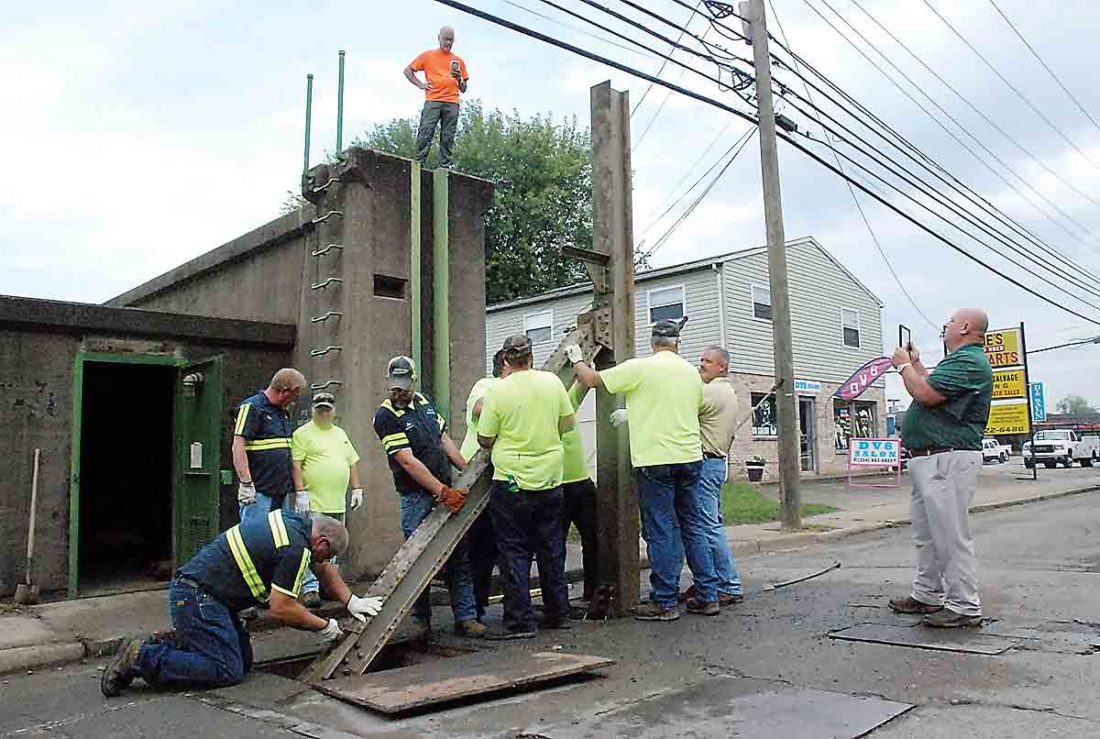 City personnel erect one of the gates to meet inspection requirements in 2017. Courtesy of News & Sentinel.