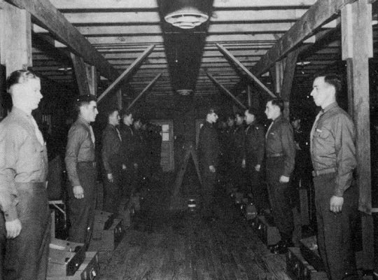 Inside the WWII era barracks- an upperclass student inspects leaders' course recruits
