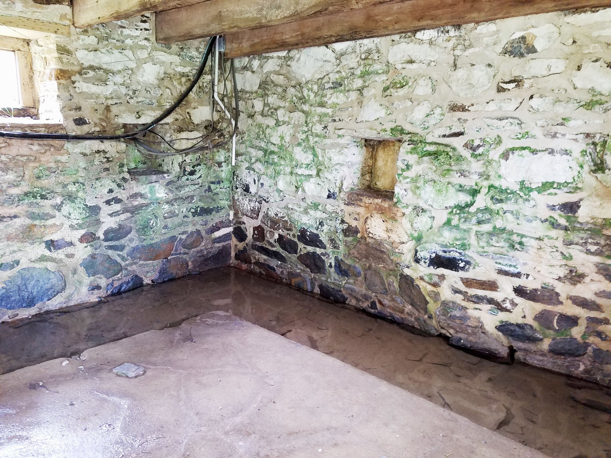 The first floor of the springhouse with the spring still flowing through it