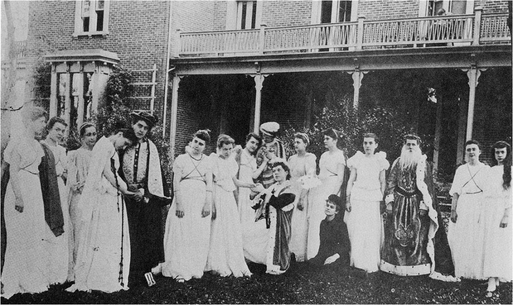 Irving College students dressed for a play standing in front of Irving Hall in 1900.