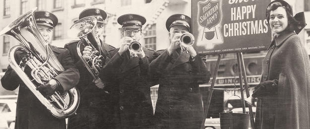 The Salvation Army Brass Band playing alongside a collection kettle, now a symbol of the Salvation Army's charitable efforts during the Christmas season