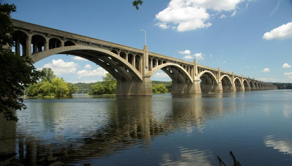 Erected in 1897, the current bridge measures 7,374 feet in length earning the title of the longest concrete arch bridge in the world. A physical and cultural staple of the region, the bridge is listed on the National Register of Historic Places.