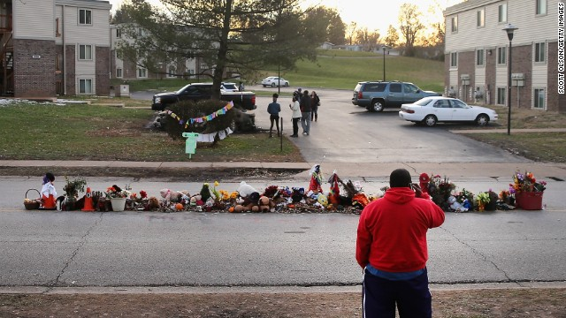 In the street where Michael Brown Jr. was fatally shot, passersby have left tokens of remembrance. This photo depicts stuffed toys and flowers which are often left to remind others that Michael was still a child at his death.