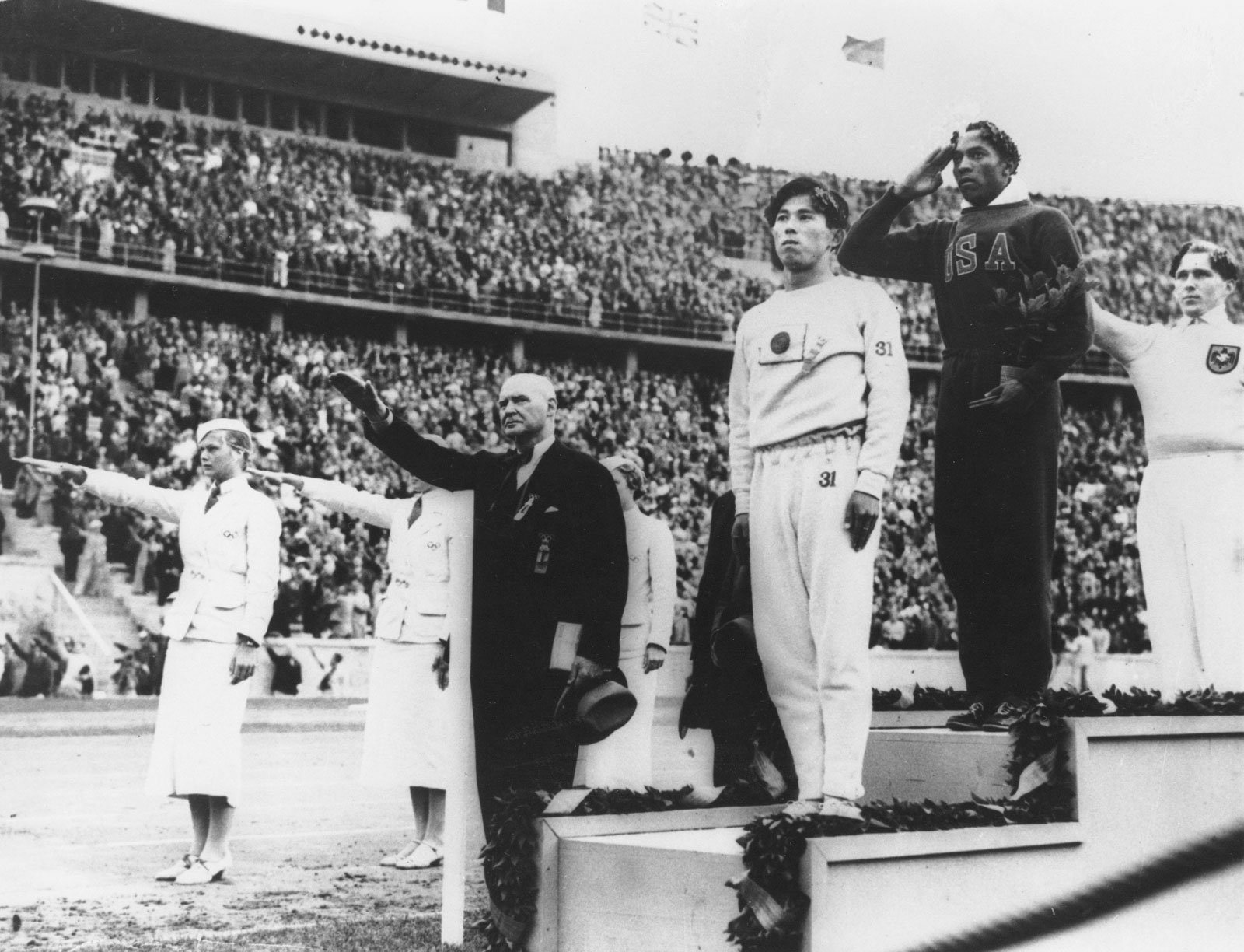 1. Jesse standing victorious while the National Anthem of the United States is played after winning gold. (Encyclopaedia Britannica).