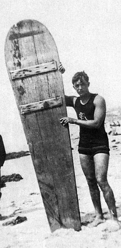 George Freeth posing with his 8 ft., 200 pound wooden surf board