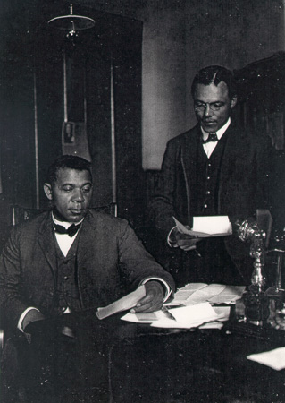 Booker T. Washington and his private secretary, Emmett J. Scott in his office, 1902