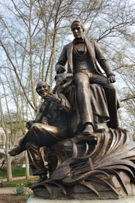 Statue of Stephen Foster and African American playing banjo below him