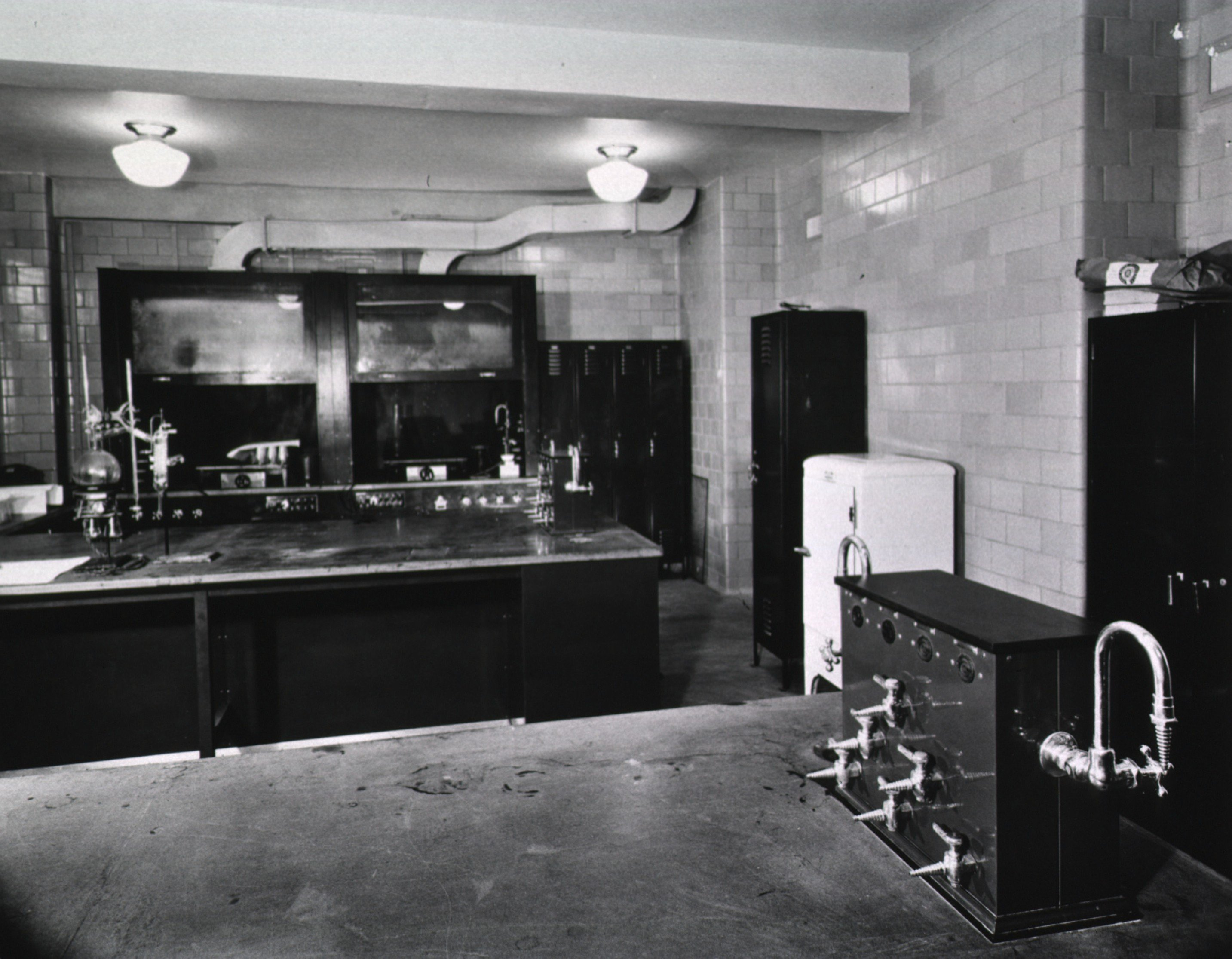c. 1938. Laboratories in Building 2 were state-of-the-art for the time. Note the fume hoods and exhaust pipes in the background.  The valves in the foreground gave researchers easy access to gas, water, and compressed air.