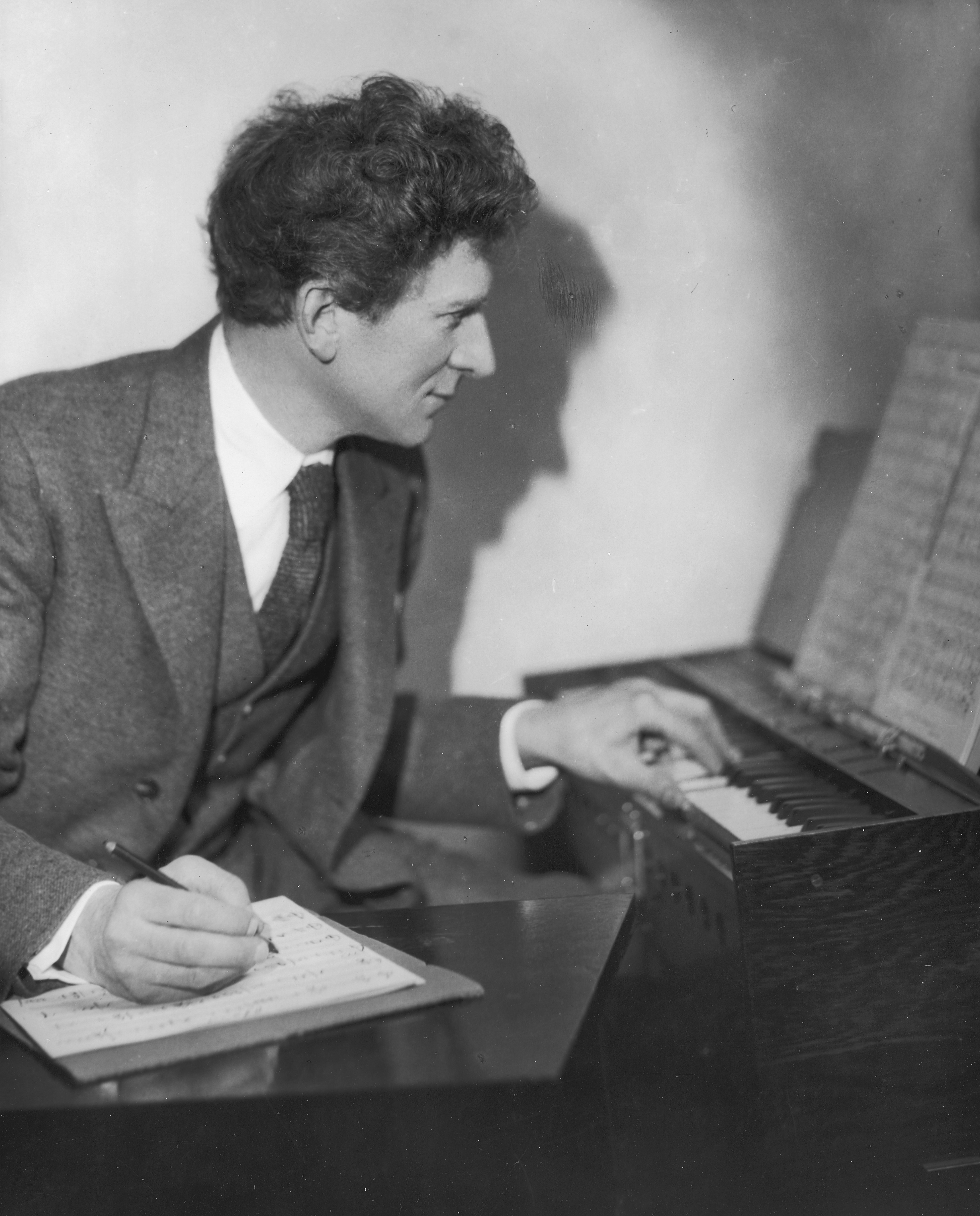 Percy Grainger practicing music in his home and studio