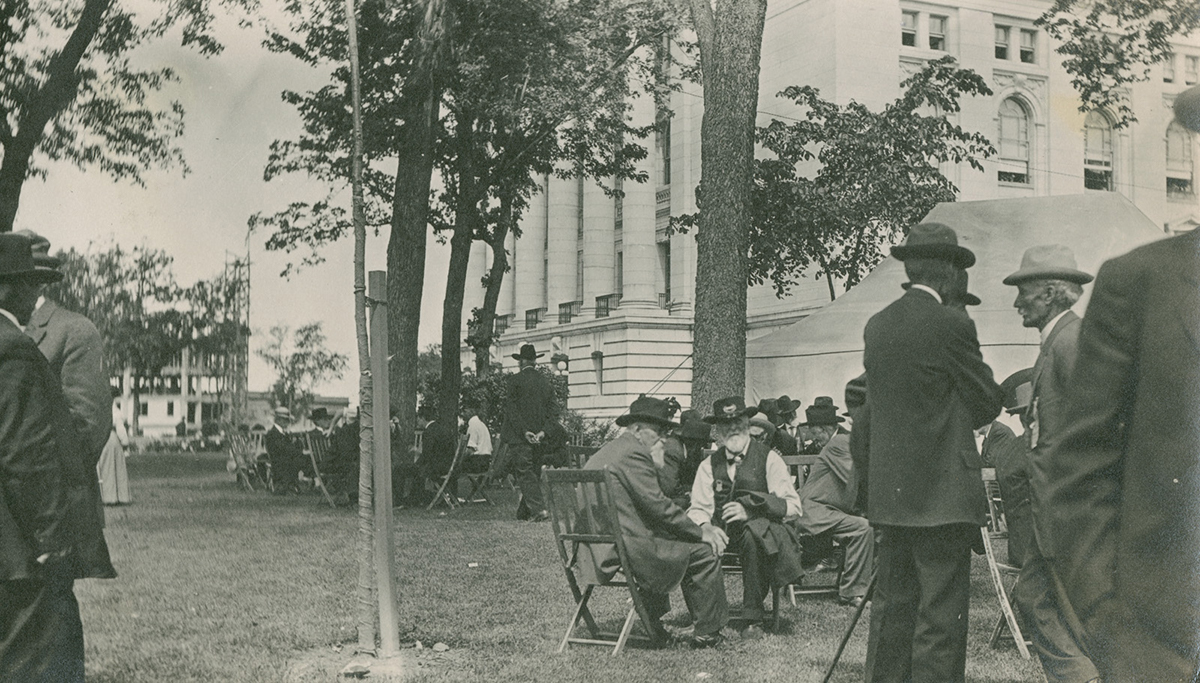 Group photograph of Civil War veterans gathered outside the Wisconsin State Capitol, Madison. The veterans are featured seated or standing in groups, wearing civilian clothes with Grand Amy of the Republic ribbons an insignia. The image was taken during a reunion in June 1914.