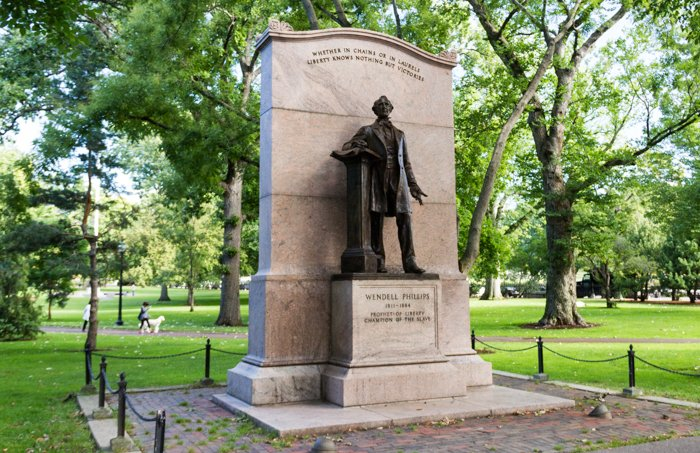 The Wendell Phillips Statue during summertime in the Boston Public Gardens.