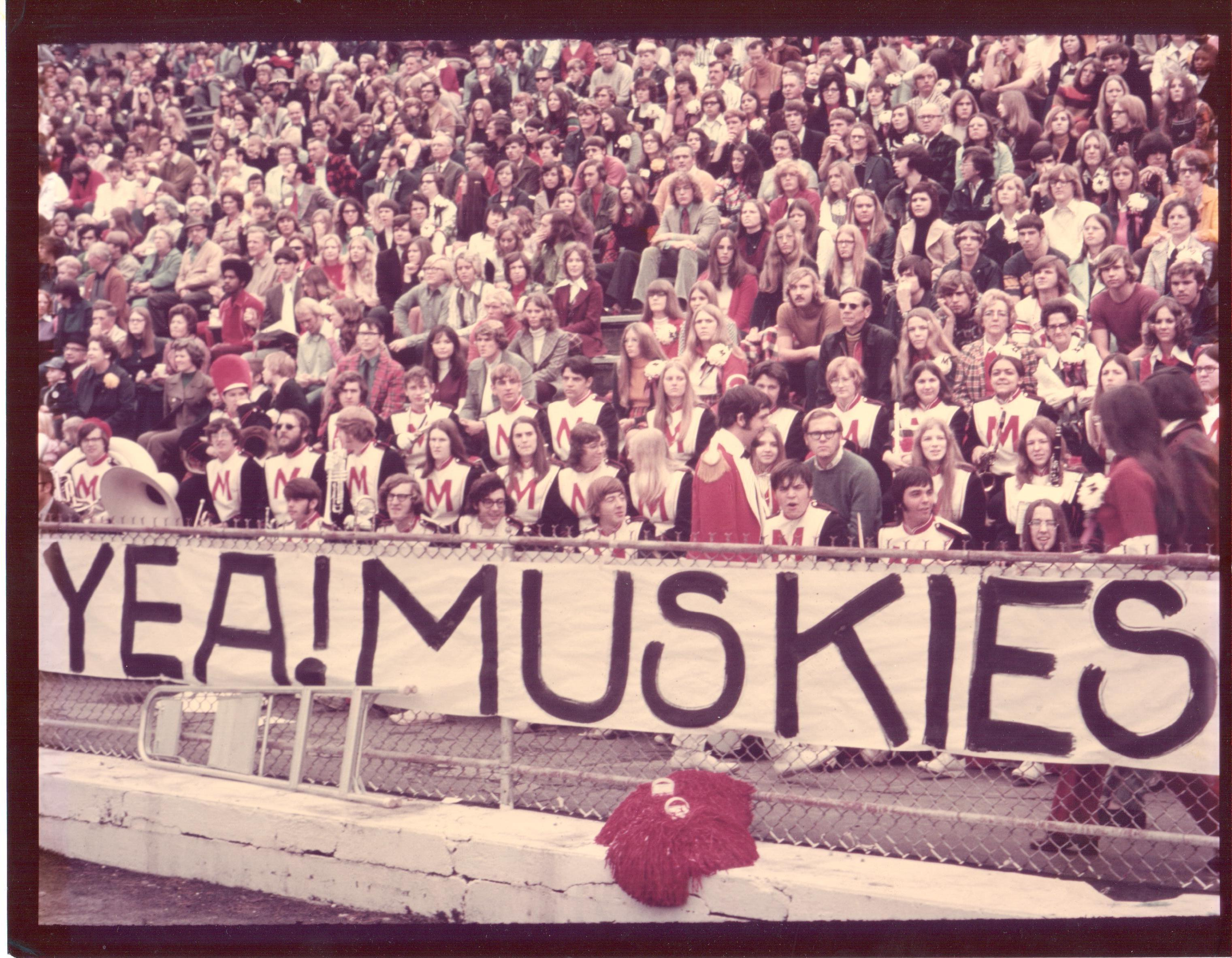 Muskingum band students cheering on their fellow muskies. This is a photo of the student band along with some Muskingum students in the background. Muskingum students made a banner to cheer on their Fighting Muskies.