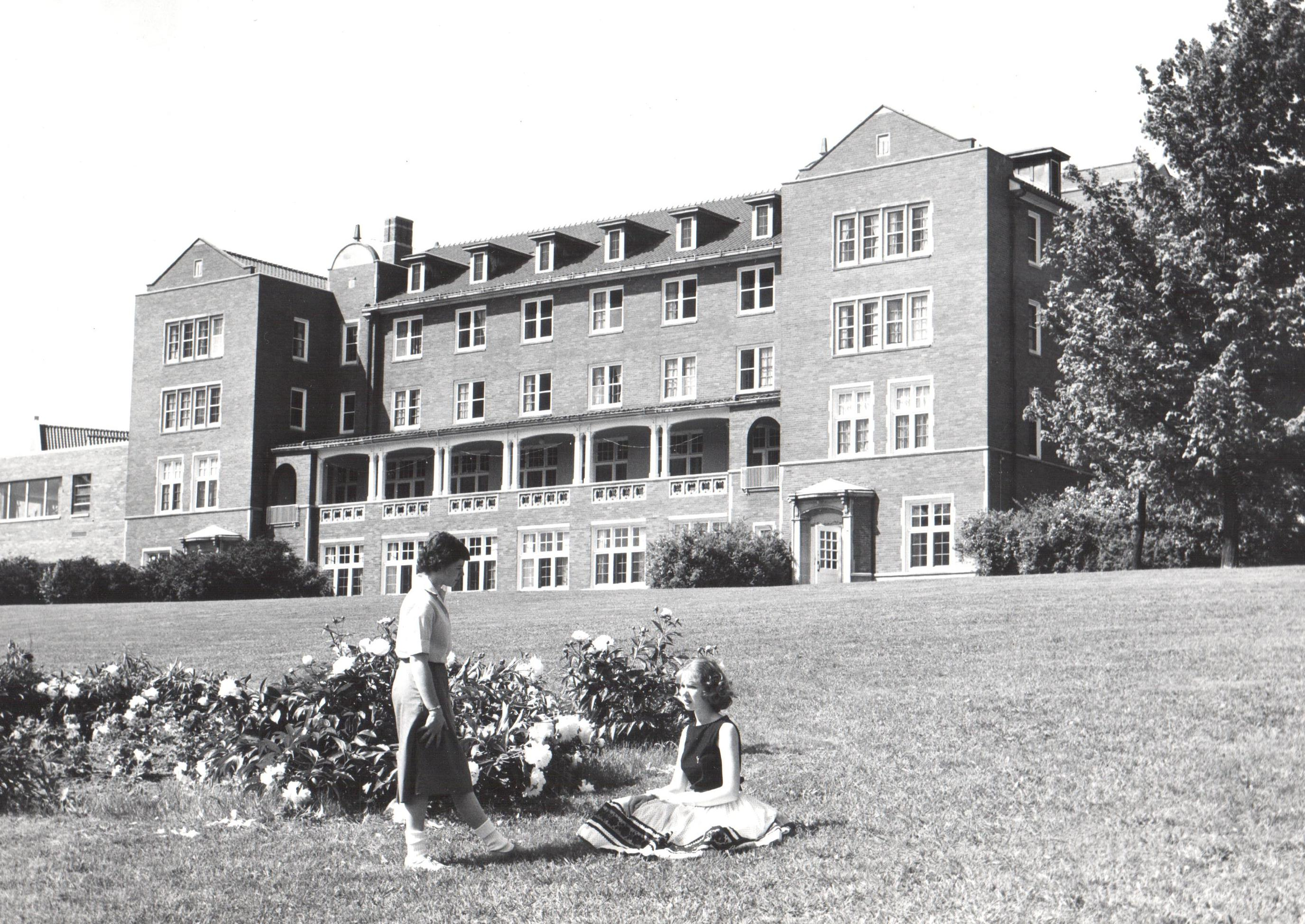Muskingum College students enjoying themselves as they sit in the lawn in front of Patton Hall