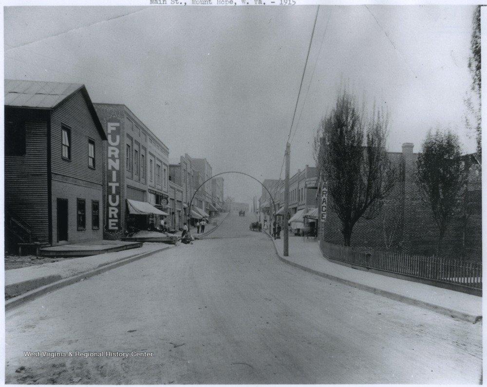 "Hardware store can be seen with ""Furniture"" sign painted on building's edge.